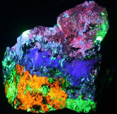 Fluorescent margarosanite, feldspar, hardystonite, clinohedrite, willemite under shortwave UV light.