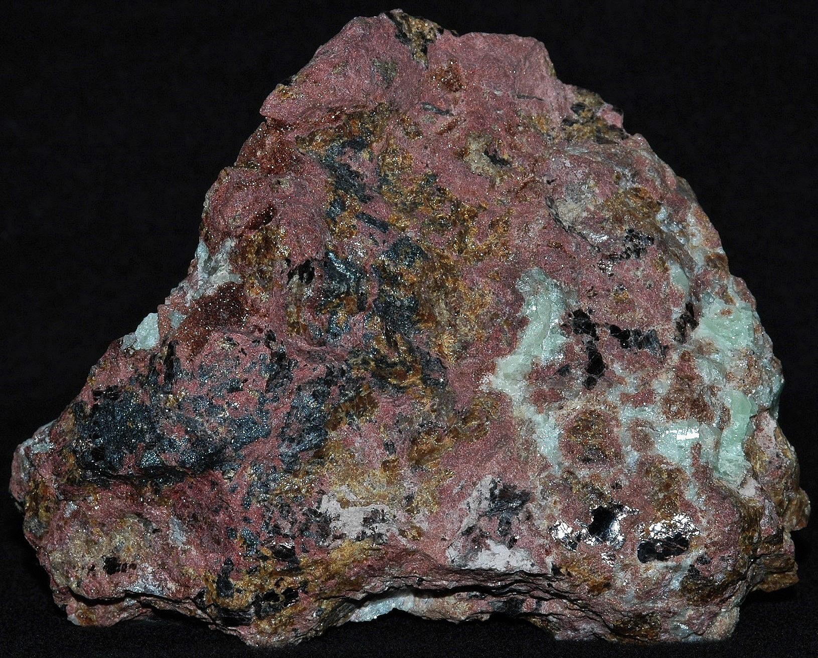 Hancockite (brick red), franklinite, andradite garnet, willemite and minor hendricksite mica from Franklin, NJ